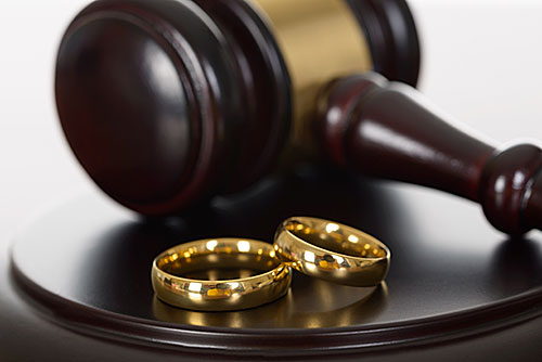 wedding rings on a desk next to a gavel