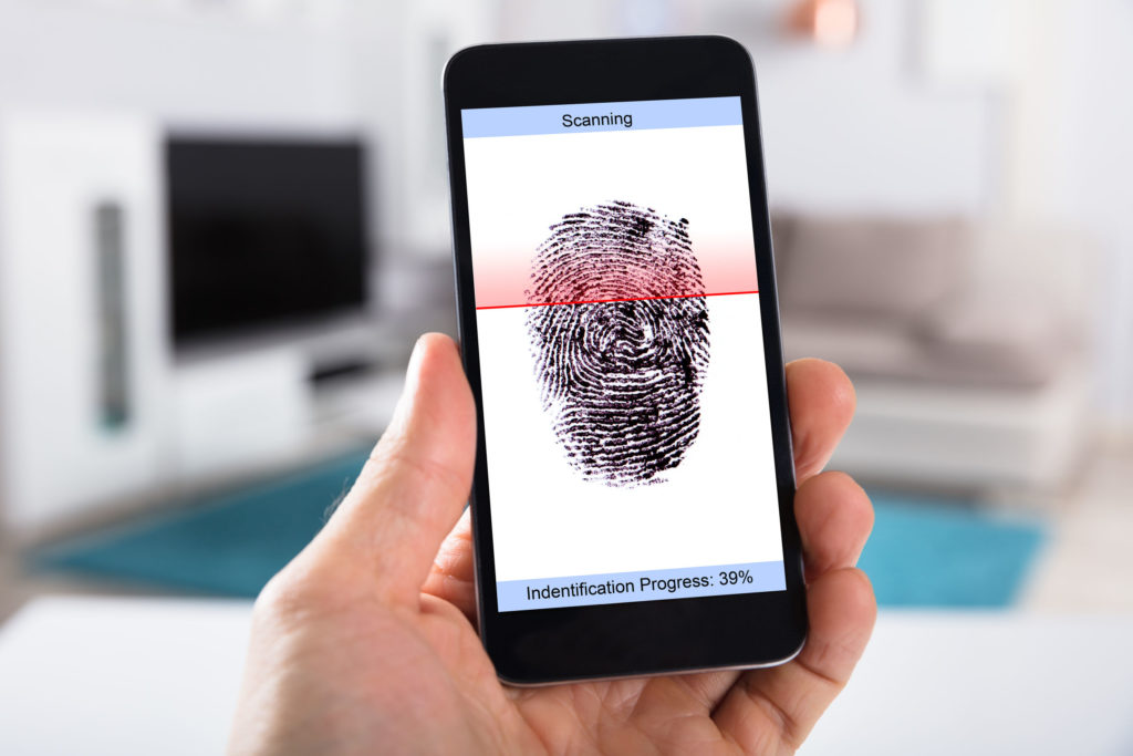 Person's Hand With Mobile Phone Showing Process Of Scanning Fingerprint On A Screen