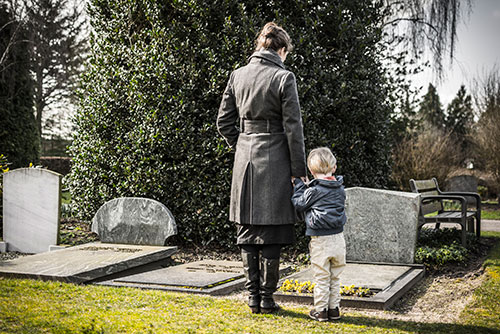 Mother and child standing next to a grave