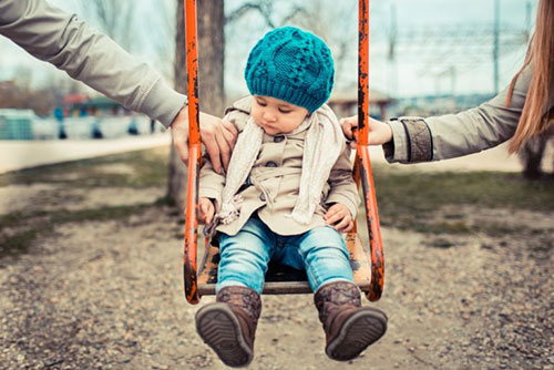 Child on swing held by mom and dad on each side