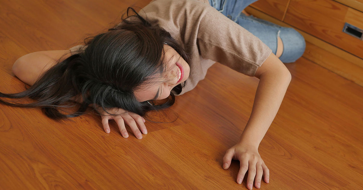 Woman laying on floor after a slip and fall