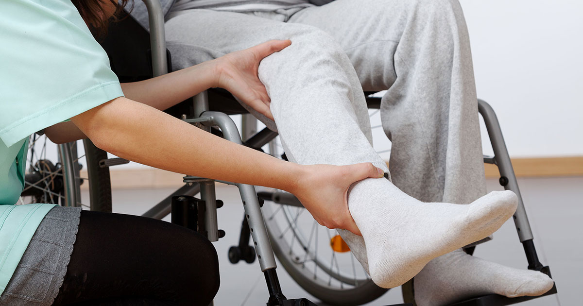 nurse holding leg of person in wheel chair