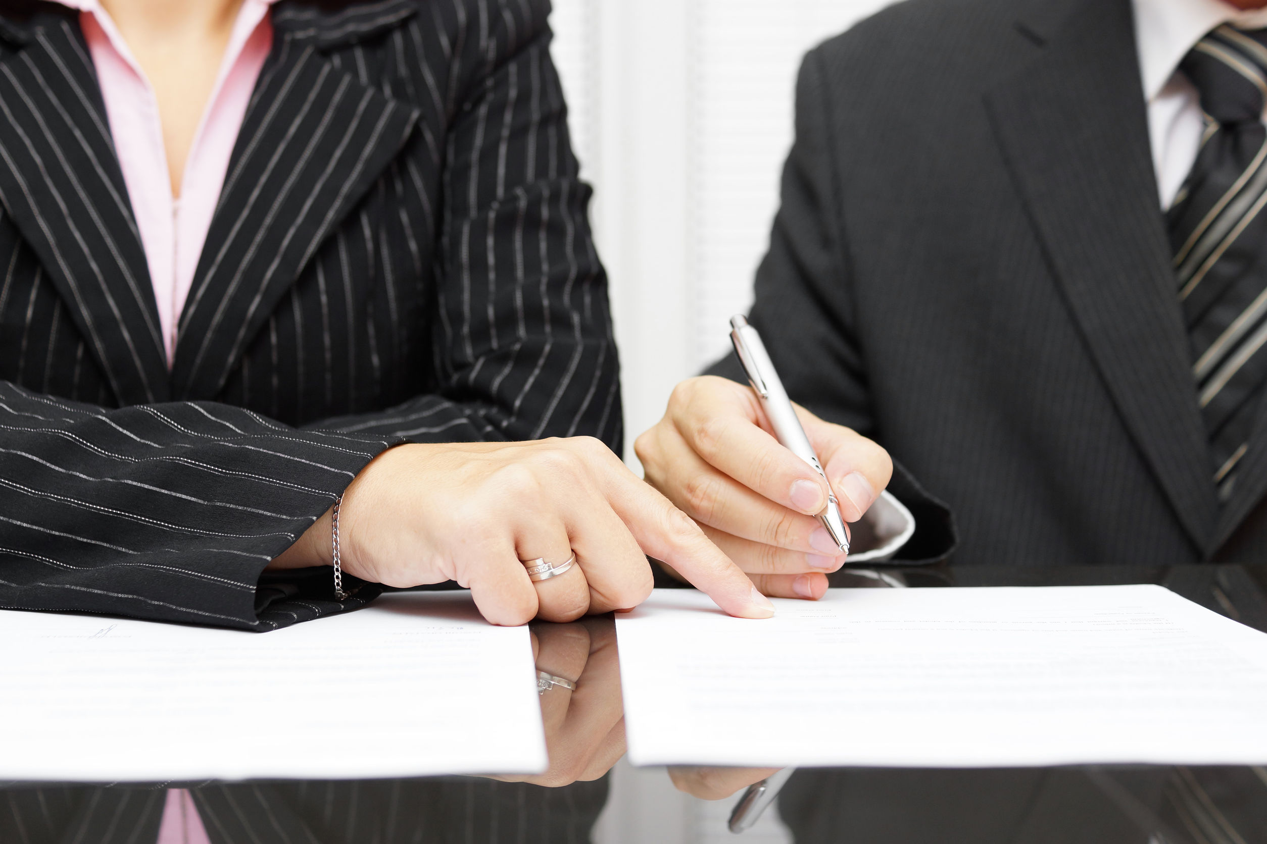 business woman shows a businessman to sign a agreement