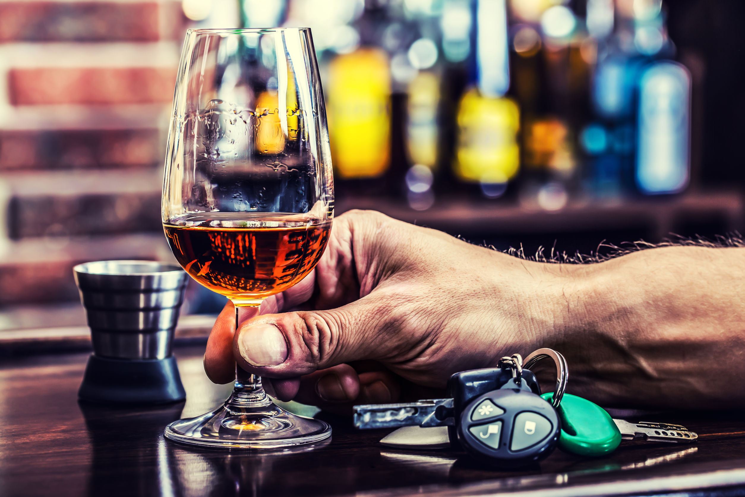 Mans hand holding alcoholic beverage with car keys next to him